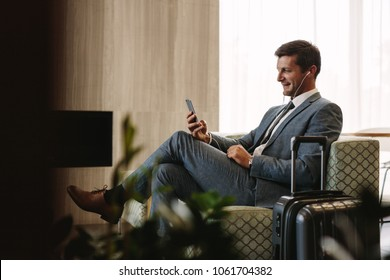Business executive making a video call by mobile phone while waiting for his flight. Businessman at airport lounge doing a video conference call from his smart phone.