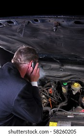 Business executive on phone at car breakdown at night