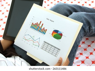 Business executive preparing presentation on corporate financial data and reports using  a tablet and wifi