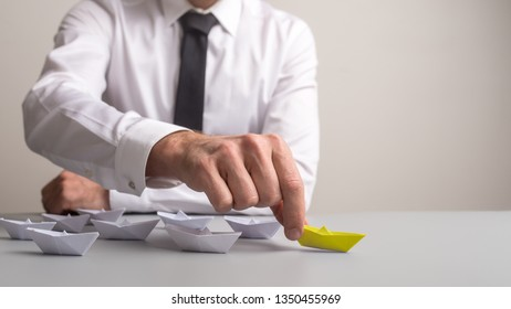 Business executive pushing forward first of many paper made origami boats that also stands out by yellow colour.