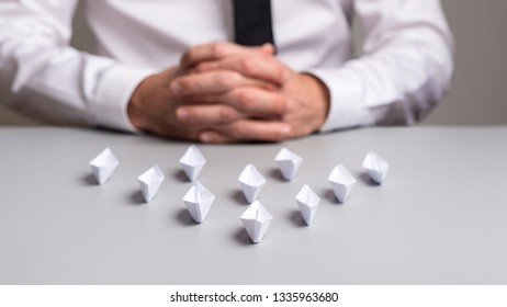 Business executive sitting at his desk with paper origami boats placed in an arrow shape in a conceptual image.