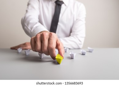 Business executive sitting at his desk pushing forward a yellow colored paper boat to advance and stand out from the crowd of other, white paper boats.