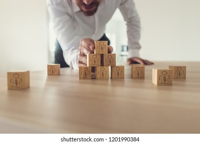 Business executive stacking wooden cubes with people icons on office desk. Conceptual of business team and human resources, retro filter effect.