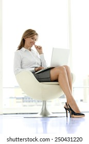 Business executive woman with laptop on knees in a lobby - Full length