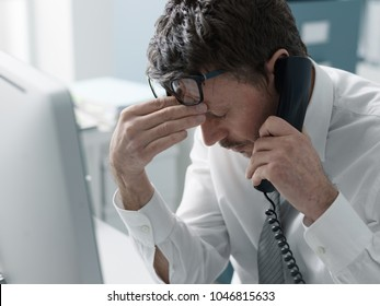 Business executive working in the office and receiving bad news on the phone, failure and crisis concept