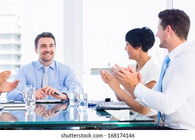 Business executives clapping around conference table in a bright office