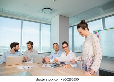 Business executives discussing with each other in conference room at office