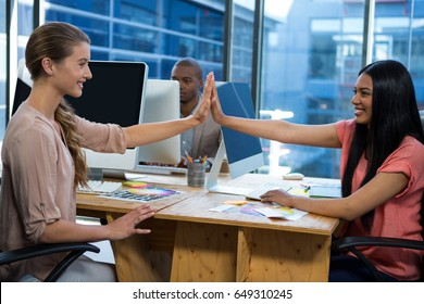 Business executives giving high five each other in office