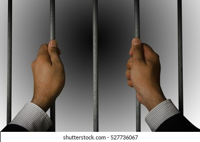 Business executives to prison with a dark background.Looking at the freedom within the prison.