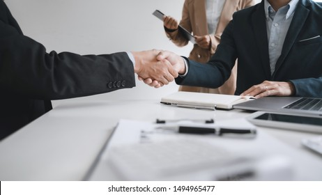 Business executives shaking hands after meeting at office, colleagues management