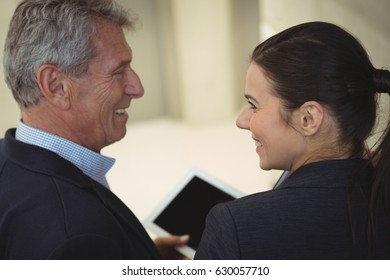 Business executives smiling while looking at each other at office