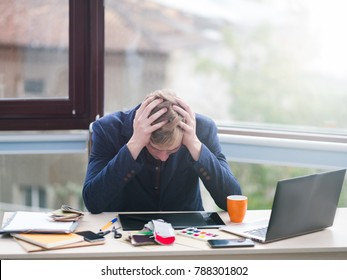 business failure. Financial crisis problems stress frustration tiredness loss concept. Worker sitting in office holds his head in hands.