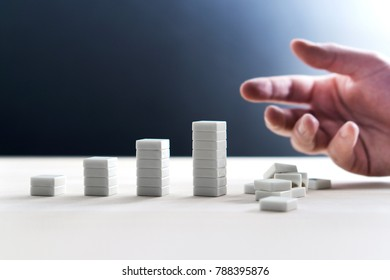 Business failure, making mistake and bankruptcy concept. Bad choice. Mess up and ruin everything. High risk and fail. All in. Bad luck. Company going bankrupt. Hand next to fallen stack of tiles.
