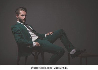 Business fashion man wearing green suit with white shirt black and tie. Sitting on wooden chair. Studio shot against grey.