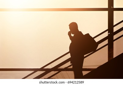 Business fat man with baggage in the terminal modern window background with sunset orange tone ,with blank copy space