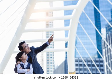 Business father showing heritage of building to his son that young boy will be heir. Little child is inheritor of property in the future. Businessman pointing finger to his property for showing son
