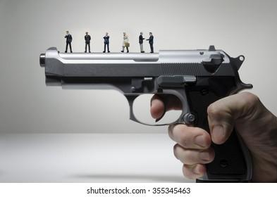 business figurines on a handgun