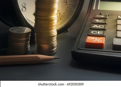 Business Finance Accounting ,Tax calculation ,Interest calculation, Calculator Coin Pencil And Vintage clock on black floor