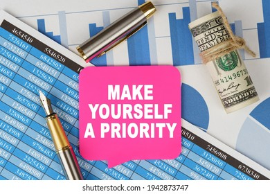 Business and finance concept. Among the financial statements and charts is a note with the text - MAKE YOURSELF A PRIORITY