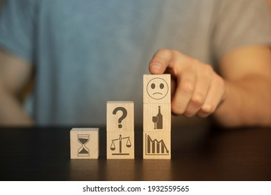Business and finance concept. Hand holds wooden wooden blocks with finance icons and business. securities, student hat,  books, time, home, car, family, question, target, gears,  securities, money, id