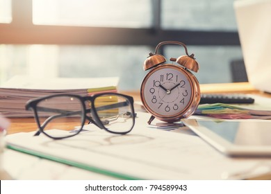Business and finance concept of office working, Closeup clock and eyeglasses on office desk
