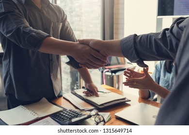 Business and finance concept of office working,Teamwork of Businessmen shaking hand after discussing investment business plan in office