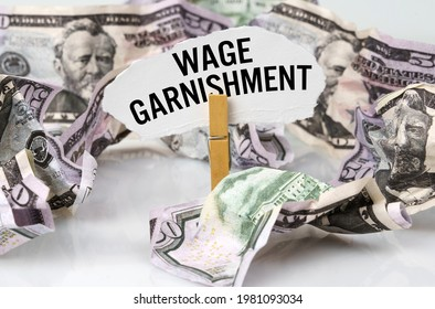 Business and finance concept. There are dollars on the table and there is a clothespin with paper on which it is written - WAGE GARNISHMENT
