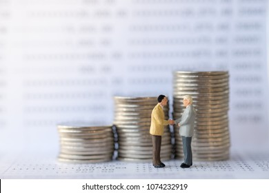 Business, finance and eCommerce concept. Two businessman miniature people figures standing, talking and hand shake on bank passbook with stack of coins.