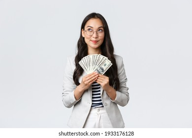 Business, finance and employment, entrepreneur and money concept. Dreamy pleased businesswoman thinking where go vacation and how invest earned dollars, hold cash and looking up thoughtful
