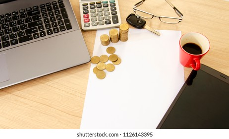 Business and finance with gold coins stack and car key and red cup coffee on wood table backgrounds