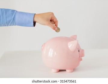 business, finance, investment, money saving and budget concept - close up of hand putting coin into piggy bank
