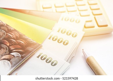 Business, finance, investment, savings or mortgage background concept ; Thai money, pen, calculator and savings account passbook on white background
