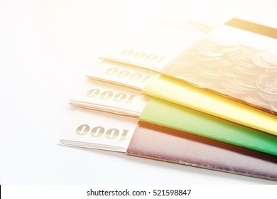 Business, finance, investment, savings or mortgage background concept ; Thai money and savings account passbook on white background