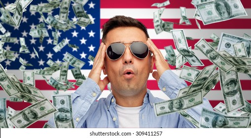 business, finance, luck, fortune and people concept - face of scared or surprised middle aged latin man in sunglasses over american flag background with heap of falling dollar money