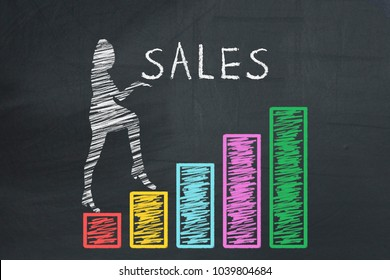 Business, finance, retail, sales concept. Business woman holding inscription SALE and climbing up on hand drawn graphs chart diagram columns