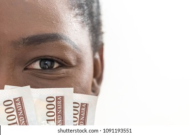 business, finance, saving, banking and people concept - close up of African American woman hiding her face behind Nigerian Naira money fan
