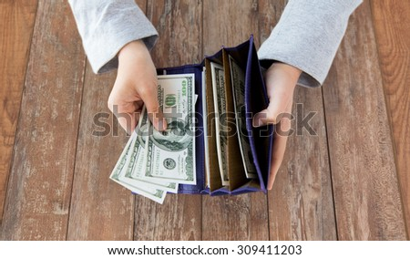 business, finance, saving, banking and people concept - close up of woman hands with wallet and us dollar money on wooden table