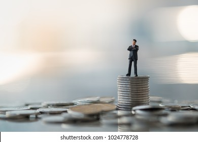 Business finance and saving concept. Businessman minature figure standing on stack of silver coins with pile of coins.