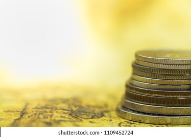 Business, Finance and saving concept. Close up of stack of many type of coins with world map as background.