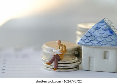Business finance, saving and home loan mortgage concept. Businessman minature figure reading a book  on stack of silver coins with mini home toy model on notebook.