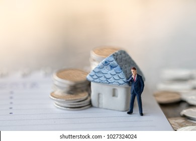 Business finance, saving and home loan mortgage concept. Businessman minature figure standing on notebook with mini house toy model and  stack of silver coins.