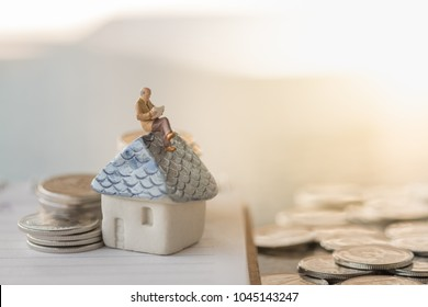 Business finance, saving and home loan mortgage concept. Businessman minature figure reading a book  on mini house toy model on notebook with stack  of silver coins.