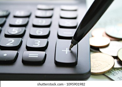 Business, finance, saving money, banking, loan, investment, taxes or accounting concept : Pen press on plus button calculator and coins on office desk table