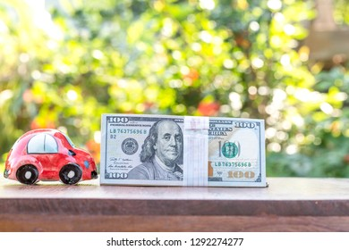 Business, finance, saving money, banking or car loan concept : Miniature car model, calculator, dollar money and saving account book or financial statement on office desk table
