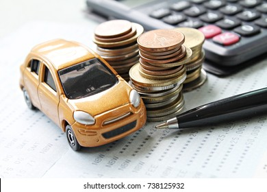 Business, finance, saving money or car loan concept : Miniature car model, coins stack, calculator and saving account book or financial statement on desk table