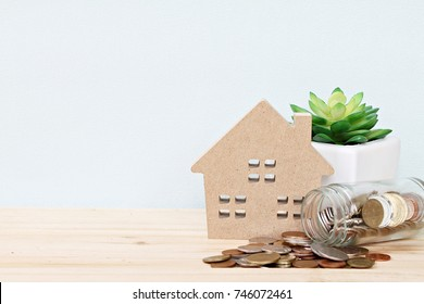 Business, finance, saving money, property ladder or mortgage loan concept : Wood house model, coins scattered from glass jar on desk table