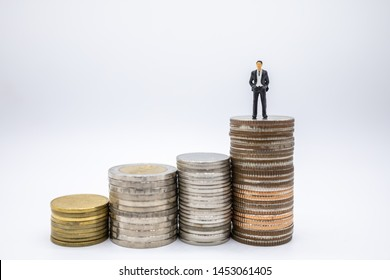 Business, Finance, Saving and secure concept. Close up of businessman minature figures standing on highest stack of coins on white background and copy space.
