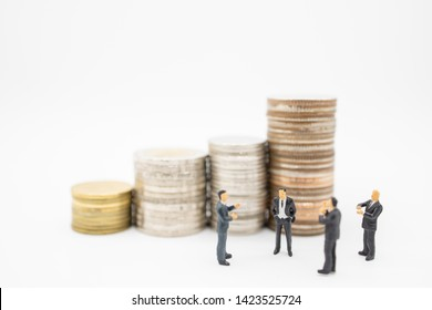 Business, Finance, Saving and teamwork concept. Close up of group of businessman minature figures standing and clap applaud appreciation with stack of coins.