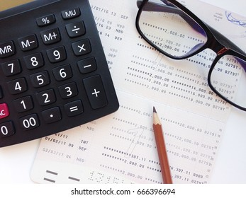 Business, finance, savings, banking or  loan concept : Pencil, calculator, eyeglasses  and savings account passbook or financial statement on white background