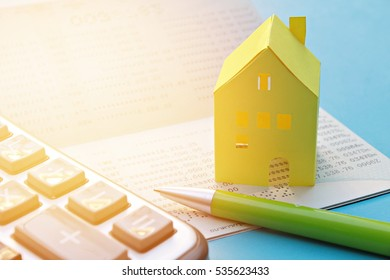 Business, finance, savings or mortgage concept : Savings account passbook, calculator, pen and yellow paper house on blue background